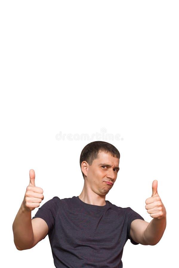 El hombre caucásico joven positivo con una cara absurda divertida, donante los pulgares sube el gesto de la aprobación y del succ imagenes de archivo