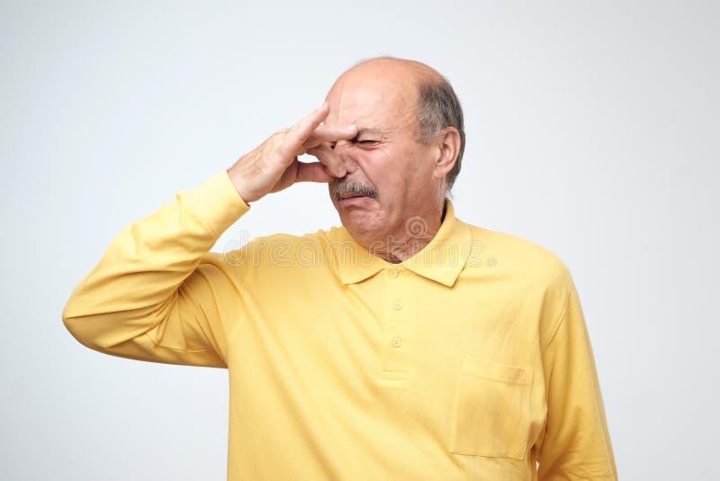 El hombre caucásico maduro en repugnancia amarillo del tshirtwith en su cara pellizca la nariz fotos de archivo libres de regalías