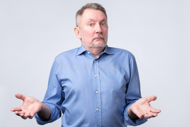 El hombre caucásico mayor confundido en camisa azul es inseguro en estudio foto de archivo
