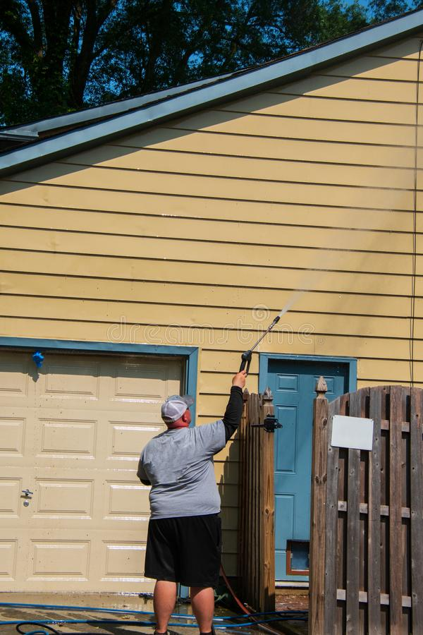 El hombre caucásico obeso es presión del espray que lava el apartadero en su casa La puerta cerrada del garaje es visible foto de archivo