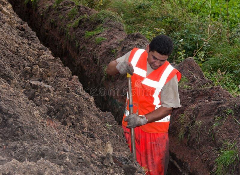 El hombre cava un foso para poner los cables foto de archivo