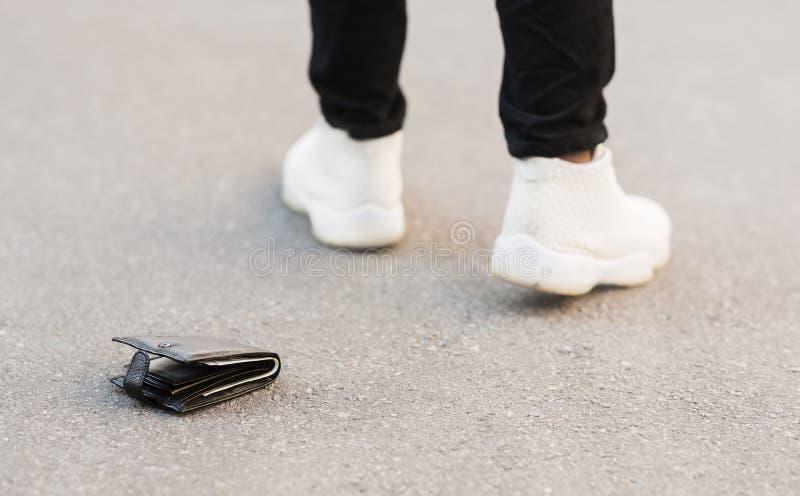 El hombre cayó accidentalmente su cartera de cuero con el dinero fotos de archivo libres de regalías