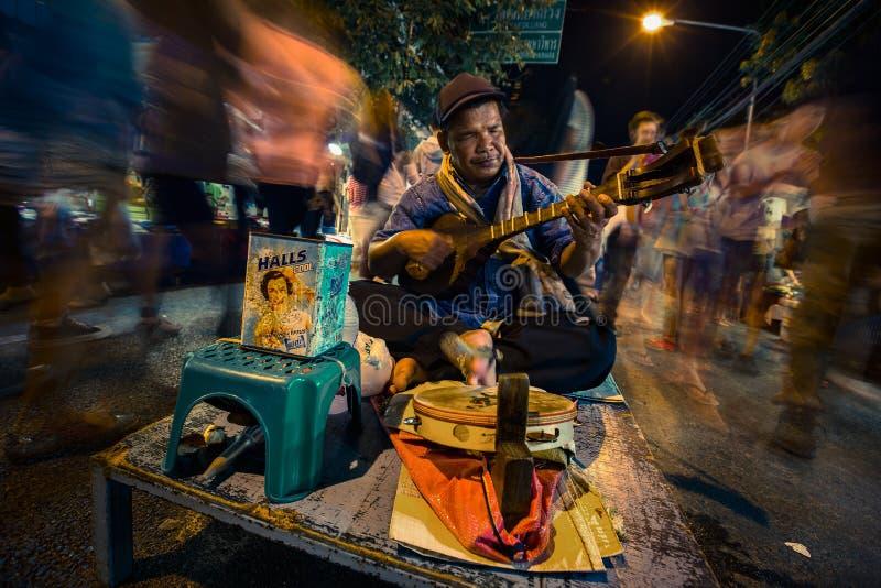 El hombre ciego toca los instrumentos múltiples para las donaciones en la calle en el mercado de la noche fotos de archivo libres de regalías