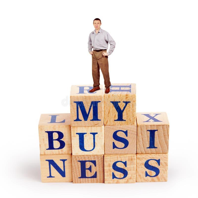 El hombre coloca sobre un montón de bloques de madera con palabras mi negocio imagenes de archivo