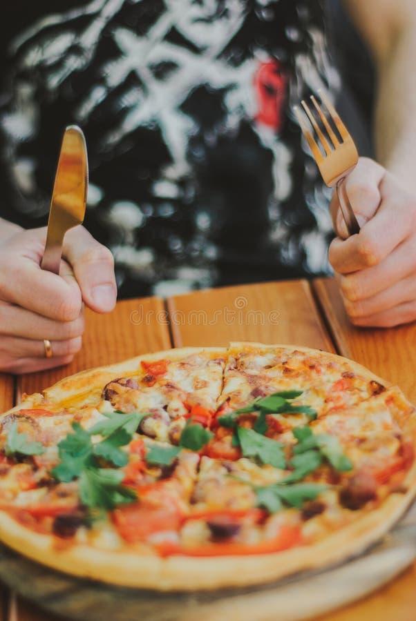 El hombre come la pizza Ciérrese encima de la pizza fotografía de archivo libre de regalías