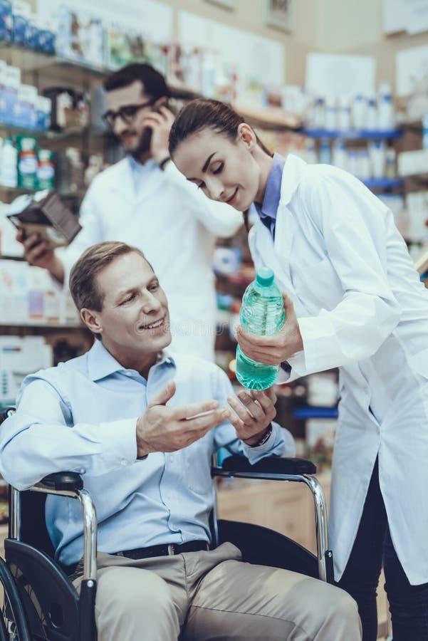 El hombre compra un agua mineral en farmacia imágenes de archivo libres de regalías