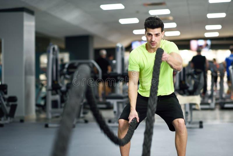 El hombre con batalla ropes ejercicio en el gimnasio de la aptitud imagenes de archivo