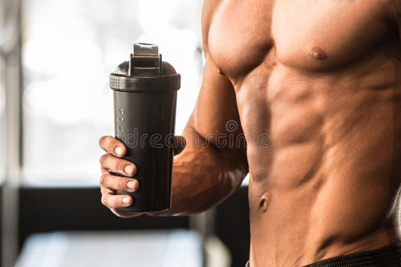 El hombre con el cuerpo perfecto sostiene la coctelera de la proteína en el gimnasio después de entrenamiento fotografía de archivo