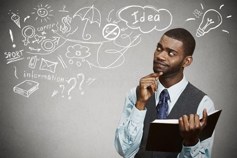 El hombre con el sueño de pensamiento del libro tiene muchas ideas que miran para arriba foto de archivo libre de regalías