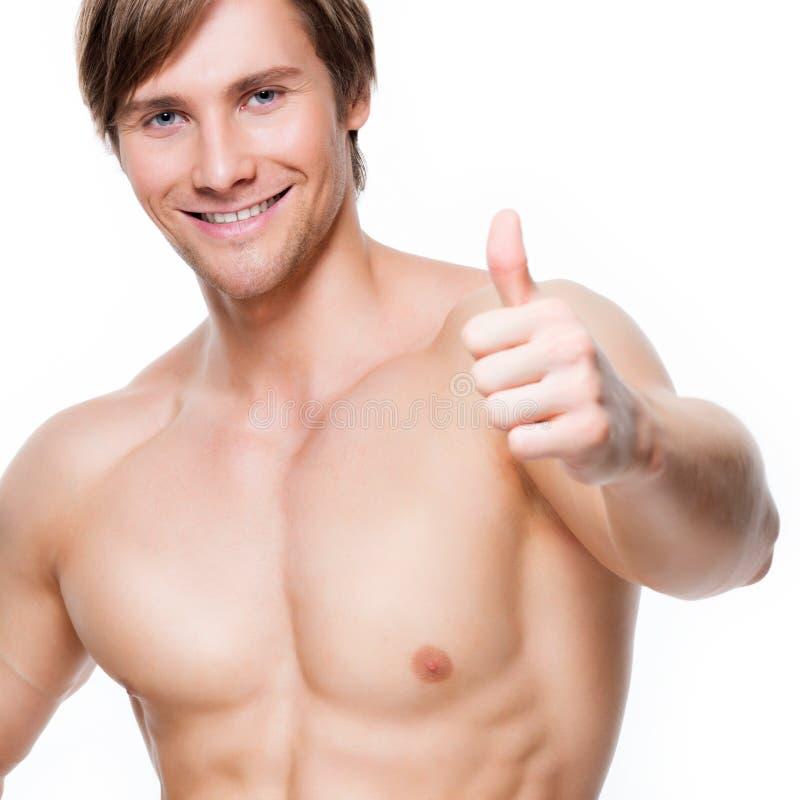 El hombre con el torso muscular muestra los pulgares encima de la muestra imagenes de archivo