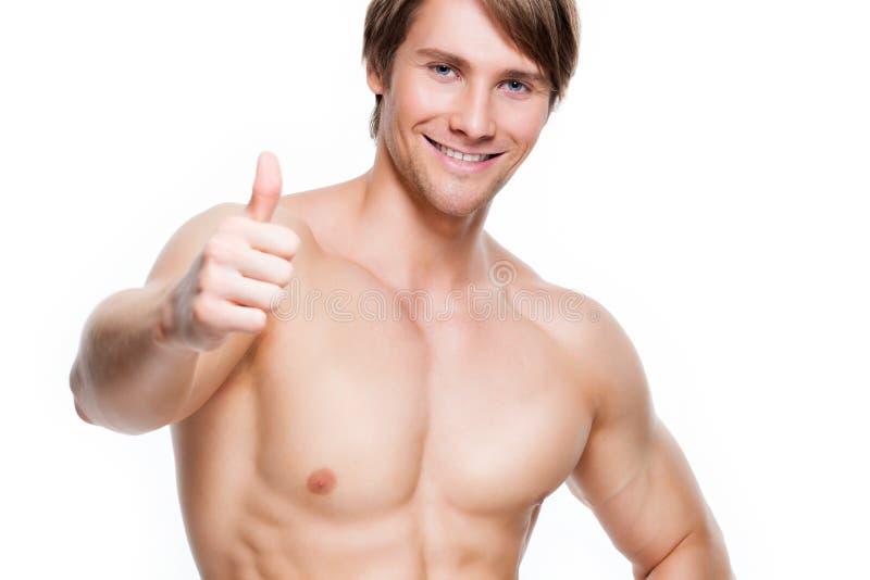 El hombre con el torso muscular muestra los pulgares encima de la muestra fotografía de archivo