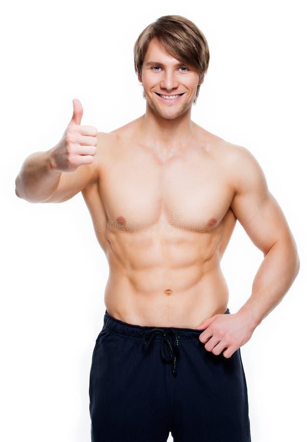 El hombre con el torso muscular muestra los pulgares encima de la muestra foto de archivo libre de regalías