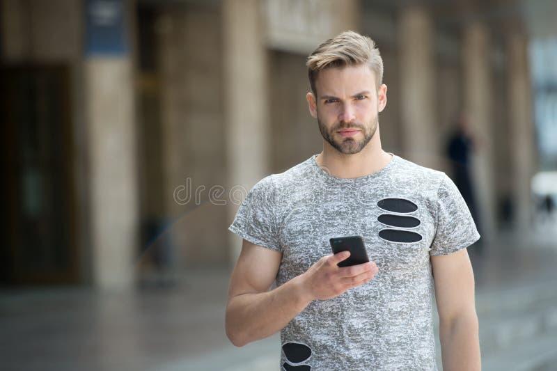 El hombre con la barba camina con el fondo urbano del smartphone Smartphone del uso del individuo para enviar el mensaje o para e imagen de archivo libre de regalías
