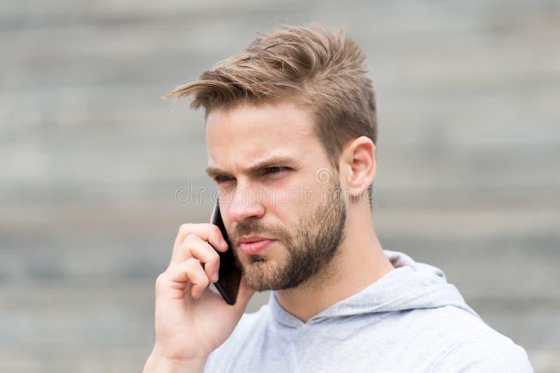 El hombre con la barba camina con el smartphone, fondo urbano con las escaleras El hombre con la barba en cara seria habla en sma foto de archivo