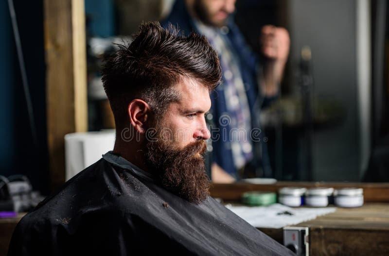 El hombre con la barba cubierta con el cabo negro se sienta en la silla de los peluqueros, fondo del espejo El inconformista con  imagen de archivo