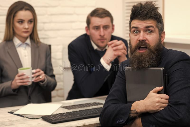 El hombre con la barba en cara sorprendida sostiene el ordenador portátil, jefes, compañeros de trabajo, colegas en fondo Hombre  fotos de archivo
