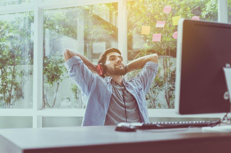 El hombre con la barba usando el auricular y escuchar la música en casa, felices comfortablemente hermosos y la sonrisa, relajan  foto de archivo libre de regalías
