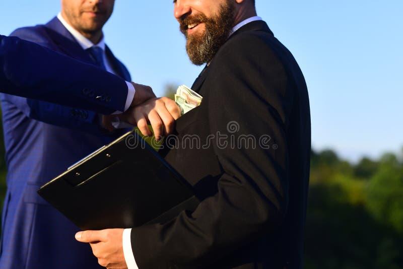 El hombre con la barba y la cara sonriente sostiene el soborno de las tomas de la carpeta foto de archivo libre de regalías