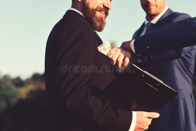 El hombre con la barba y la cara sonriente sostiene el soborno de las tomas de la carpeta fotos de archivo libres de regalías