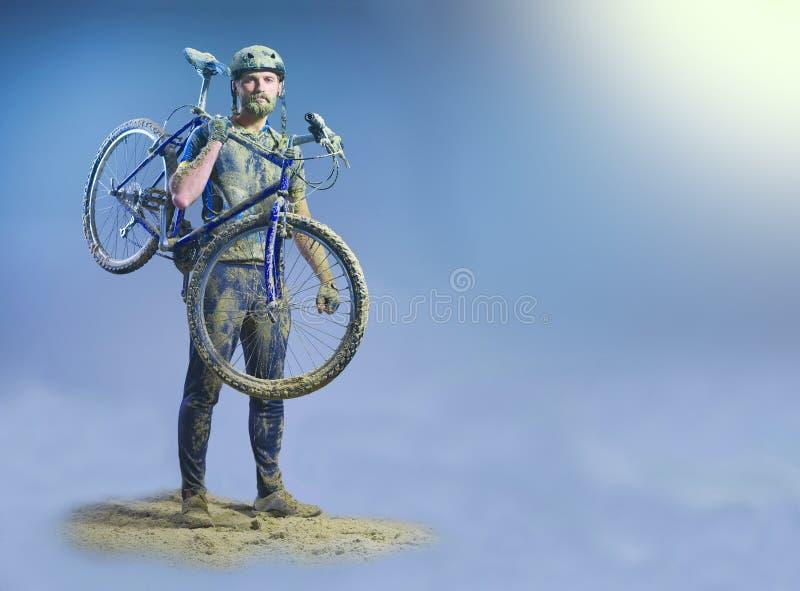El hombre con la bici en la arena que se coloca en fondo abstracto collage fotos de archivo