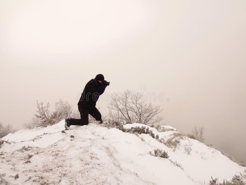El hombre con la cámara en roca nevosa hace la foto del paisaje imagen de archivo libre de regalías