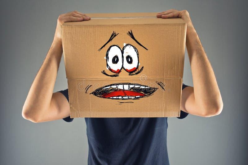 El hombre con la caja de cartón en su cabeza y mirada aterrorizada skethed fotografía de archivo libre de regalías