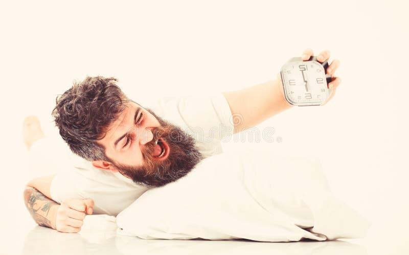 El hombre con la cara de grito miente en la almohada cerca del despertador fotografía de archivo libre de regalías