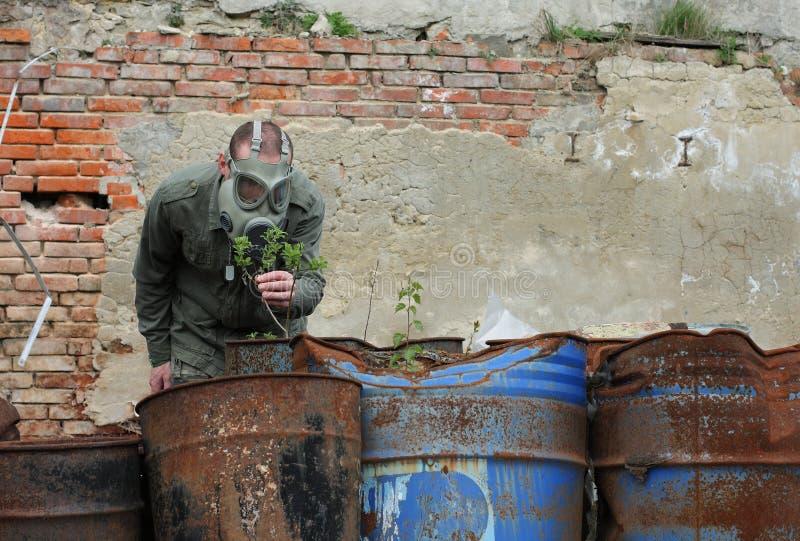 El hombre con la careta antigás y la ropa militar explora la pequeña planta imágenes de archivo libres de regalías