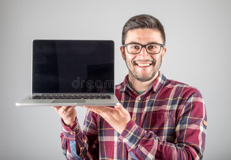 El hombre con la demostración del ordenador portátil screeen imagen de archivo libre de regalías