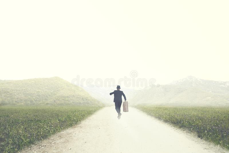 El hombre con la maleta corre rápidamente en un camino abandonado a un destino desconocido fotografía de archivo libre de regalías