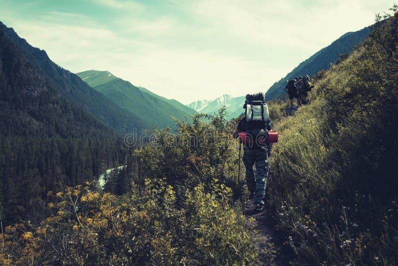 El hombre con la mochila que camina en montañas viaja deporte al aire libre del alpinismo de las vacaciones activas de la aventur foto de archivo
