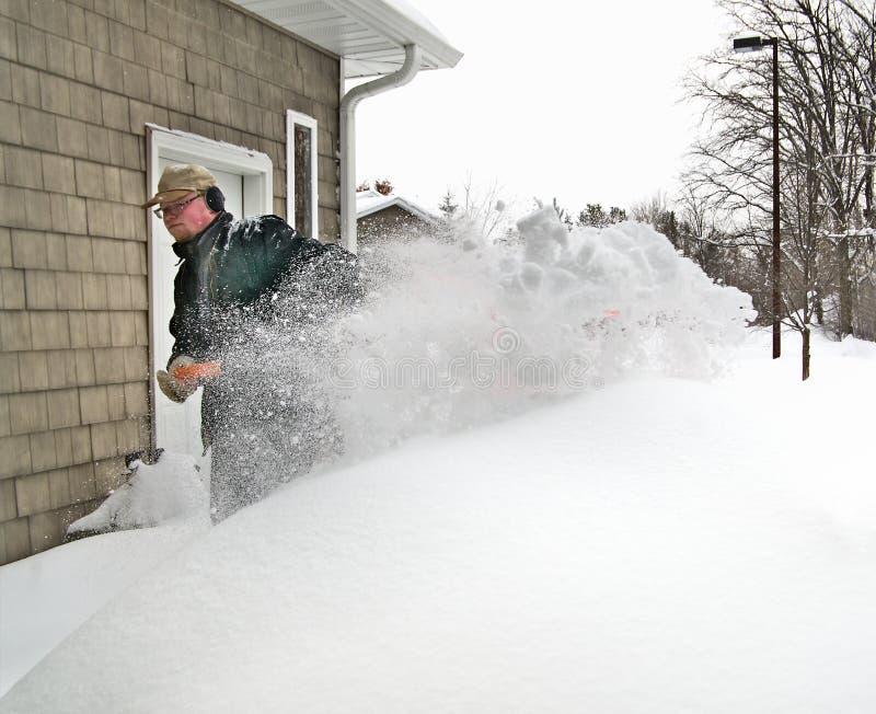 El hombre con la pala limpia nieve profunda de la acera después de tormenta de la nieve del invierno fotos de archivo libres de regalías