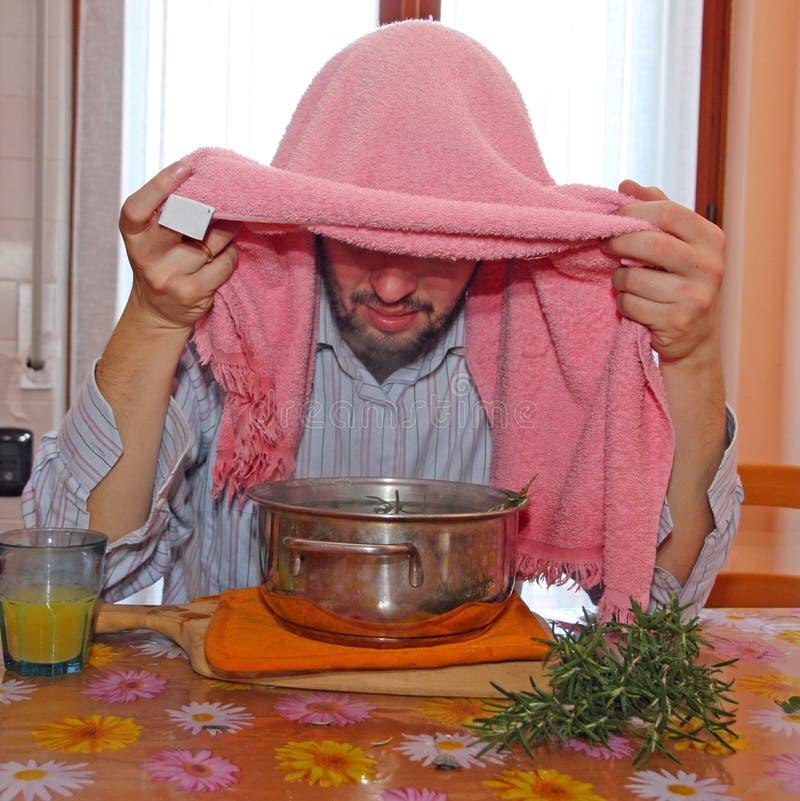 El hombre con la toalla respira los vapores del bálsamo para tratar fríos fotos de archivo libres de regalías