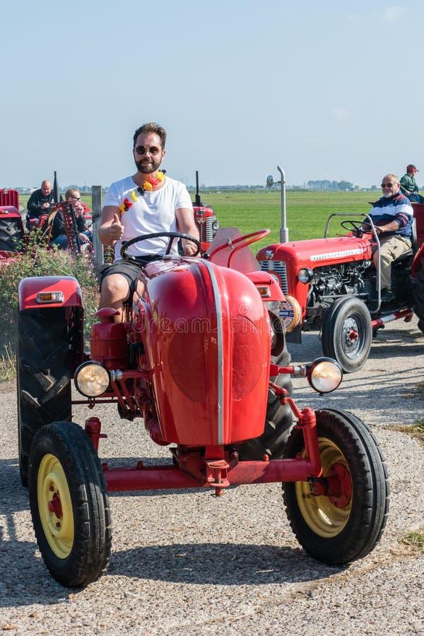 El hombre con las gafas de sol y la camiseta blanca en el tractor rojo da los pulgares-para arriba mientras que él comienza a con imagen de archivo