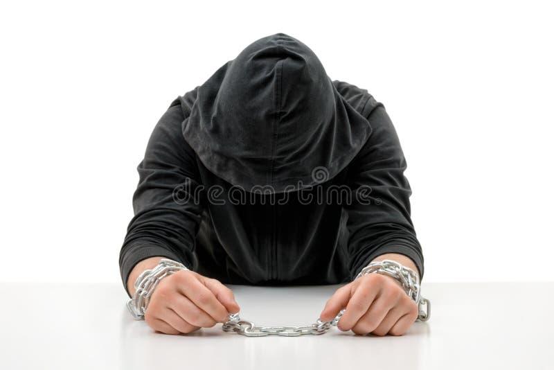 El hombre con las manos en cadenas está sentando la cabeza arqueada imagenes de archivo