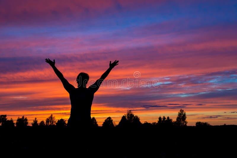 El hombre con las manos sube la silueta con puesta del sol colorida foto de archivo
