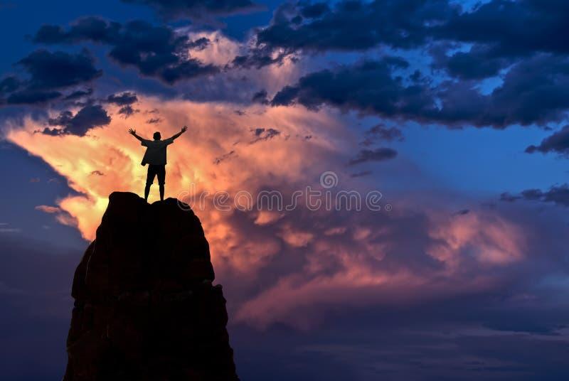 El hombre con los brazos aumentó en el concepto del éxito del ganador del cielo fotografía de archivo