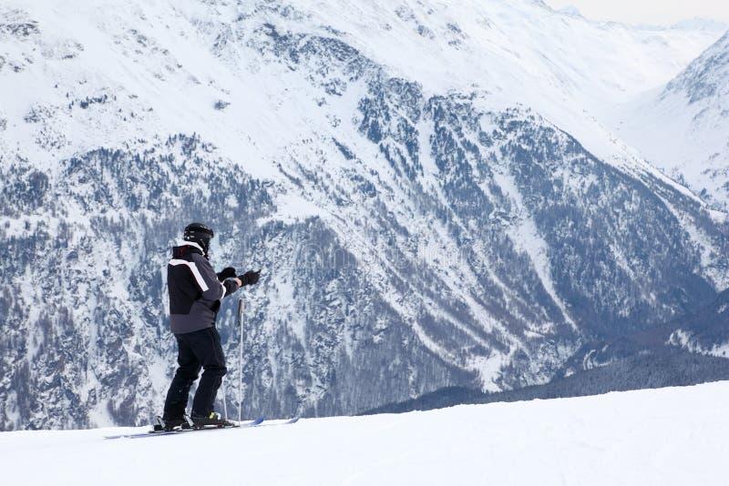 El hombre con los esquís mira y se prepara para la cuesta fotografía de archivo