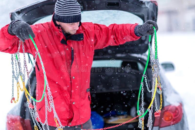 El hombre con los guantes instala cadenas de nieve en el neumático del coche en invierno en nieve imagenes de archivo
