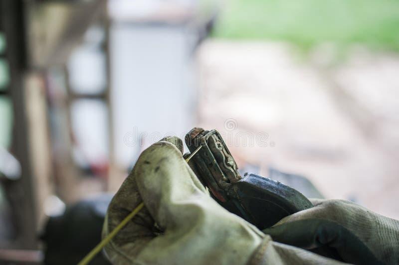 El hombre con los guantes protectores puso el electrodo para soldar con autógena fotografía de archivo libre de regalías