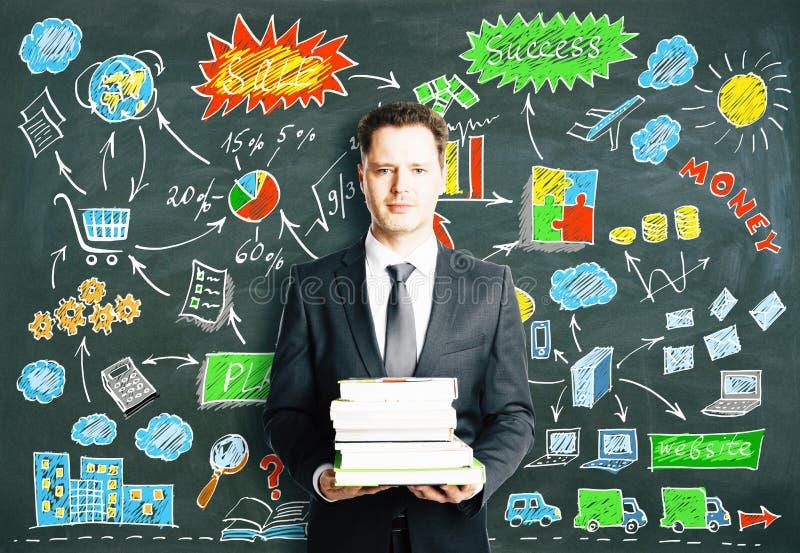 El hombre con los libros y el negocio diagram exhausto en concepto de la pizarra fotos de archivo