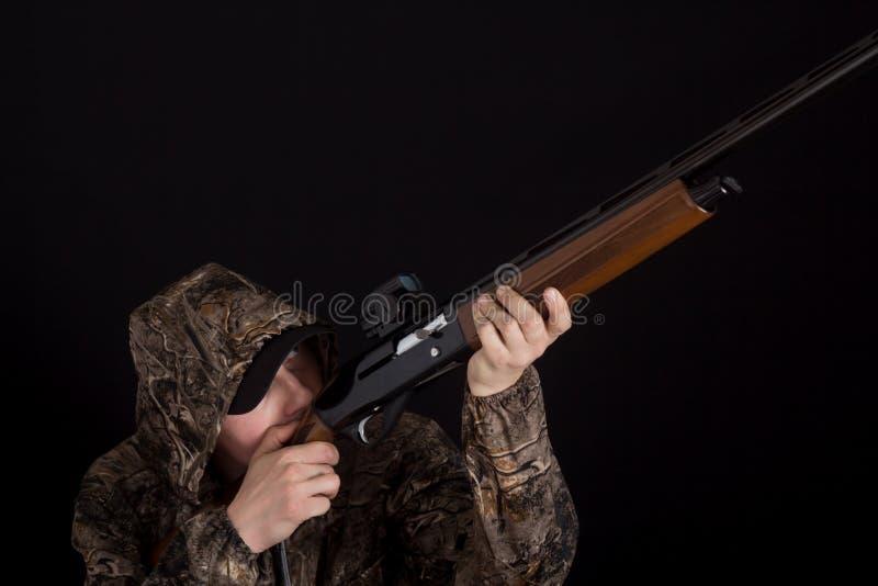 El hombre con los objetivos del arma Cazador en ropa del camuflaje con una escopeta en un fondo negro Militar con las armas Copie imagen de archivo libre de regalías