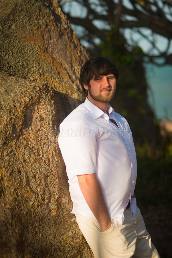 El hombre con el pelo negro en una camisa blanca se coloca cerca de la pared en las zonas tropicales en la puesta del sol imagen de archivo libre de regalías