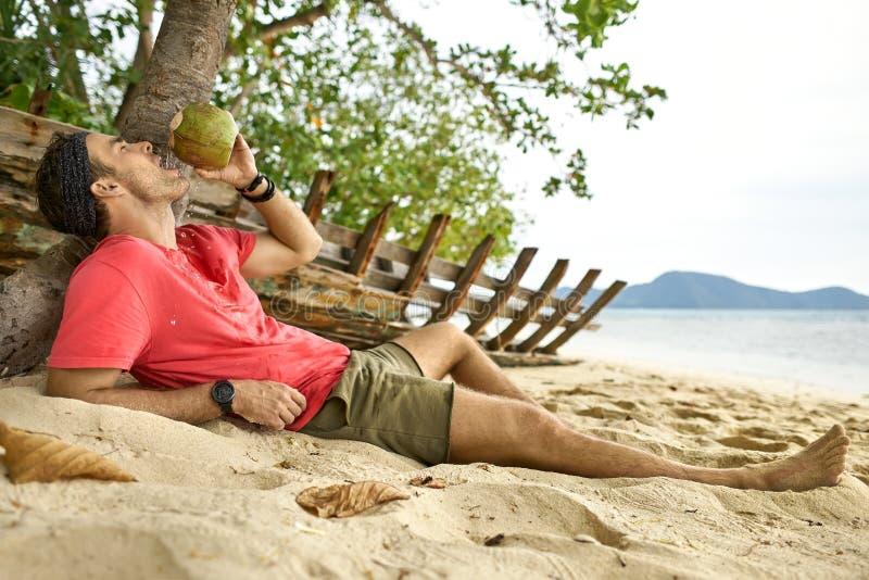 El hombre con rastrojo está bebiendo del coco en la playa de la arena fotos de archivo