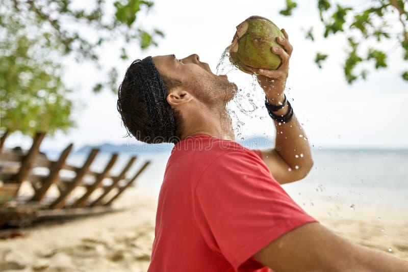El hombre con rastrojo está bebiendo del coco en la playa de la arena imagenes de archivo