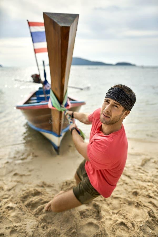 El hombre con rastrojo está tirando del barco de madera por la cuerda en la playa de la arena imagenes de archivo