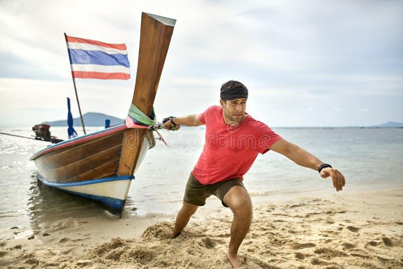 El hombre con rastrojo está tirando del barco de madera por la cuerda en la playa de la arena fotografía de archivo