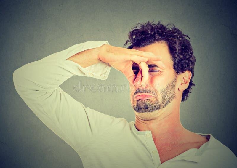 El hombre con repugnancia en cara pellizca la nariz, algo apesta el mún olor imagen de archivo
