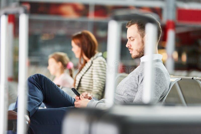 El hombre con smartphone está esperando en zona de descanso del aeropuerto foto de archivo