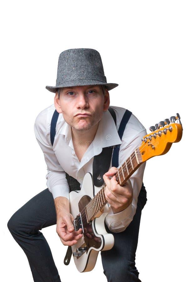 El hombre con el sombrero toca la guitarra eléctrica imagen de archivo libre de regalías
